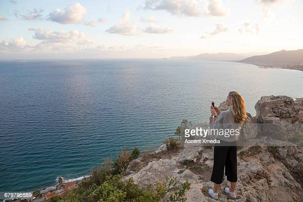 Young woman takes pic from rocky knoll above sea