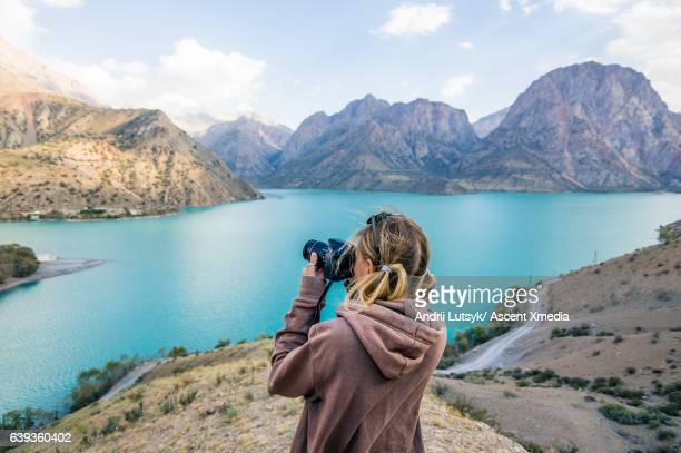 young woman takes picture across mountain lake - photographer stock pictures, royalty-free photos & images