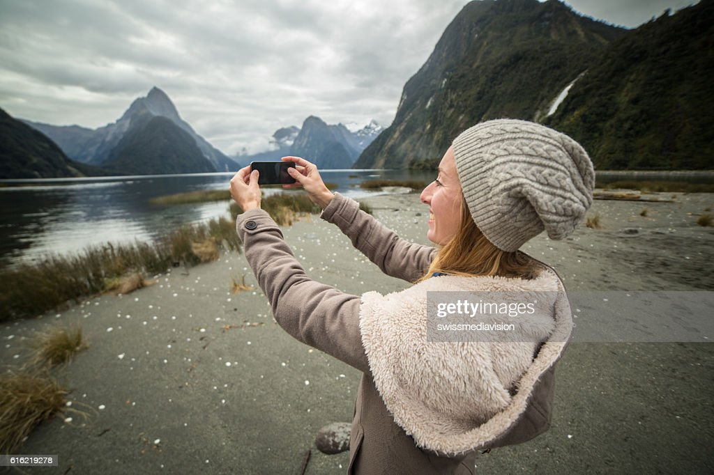 Young woman takes picture of mountain landscape with mobile phone : Stock Photo