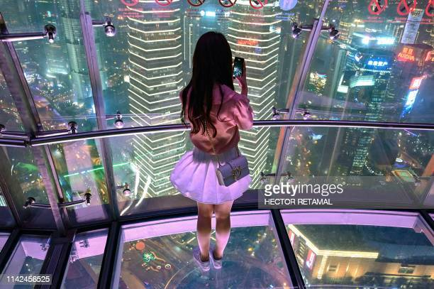 A young woman takes pictures of the city with her mobile phone from the glassfloor observation platform in the Oriental Pearl Tower in the financial...