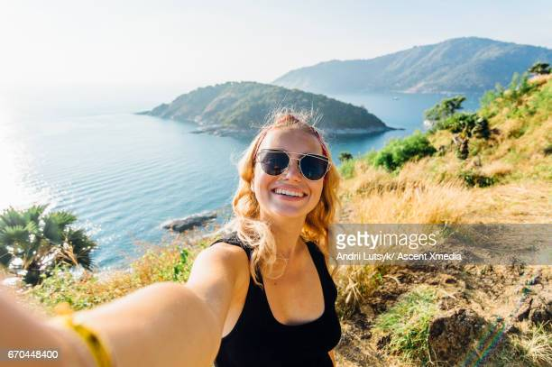 Young woman takes selfie, on hillside above sea