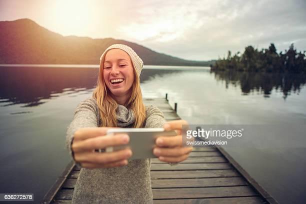 Young woman takes selfie portrait on wooden pier