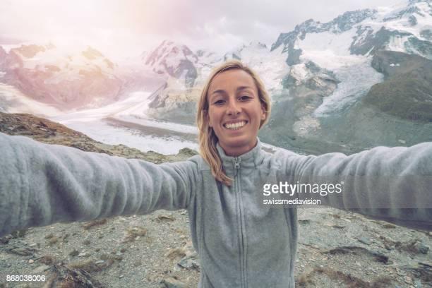 Junge Frau nimmt Selfie Portrait mit Gletscher im Hintergrund