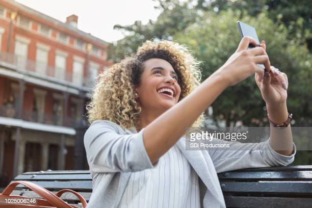 young woman takes selfie while on vacation - photo messaging stock photos and pictures