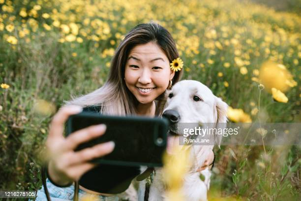 young woman takes selfie with her dog in flower filled field - korean ethnicity stock pictures, royalty-free photos & images