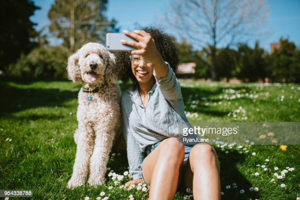 a young woman takes selfie with pet poodle dog - black shorts stock pictures, royalty-free photos & images