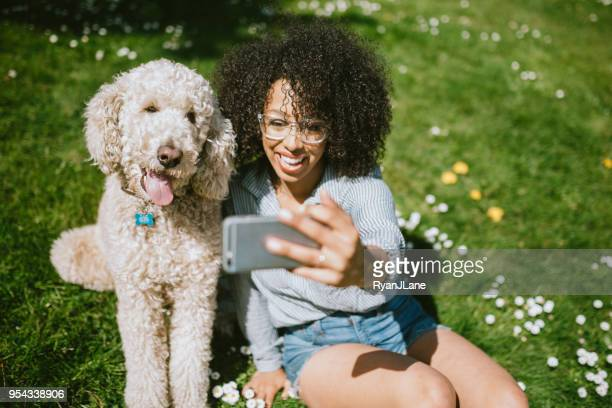 a young woman takes selfie with pet poodle dog - poodle stock pictures, royalty-free photos & images