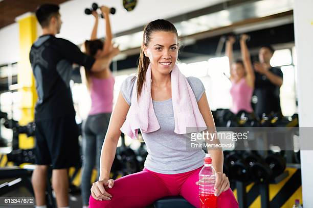 Young woman taking a break from exercising at gym