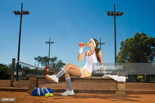 Young woman taking a break from playing tennis