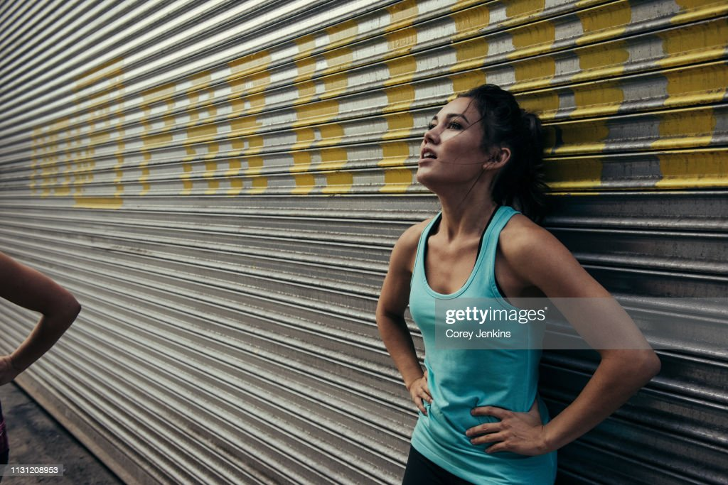 Young woman taking a break from running, against shutter : Stock Photo