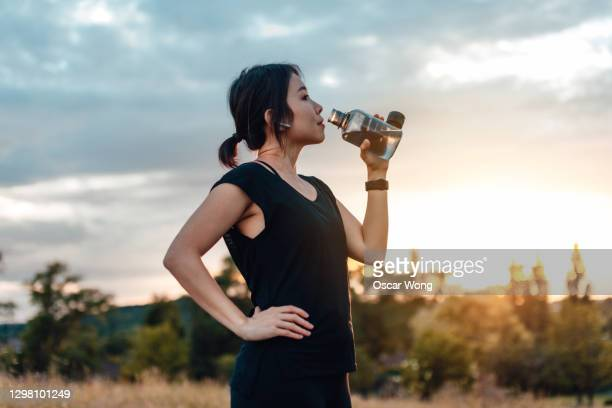 young woman taking a break from running, against sunset - drinking stock pictures, royalty-free photos & images