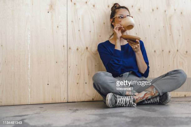 young woman taking a break in office, drinking coffee from a wooden cup - ruhen stock-fotos und bilder