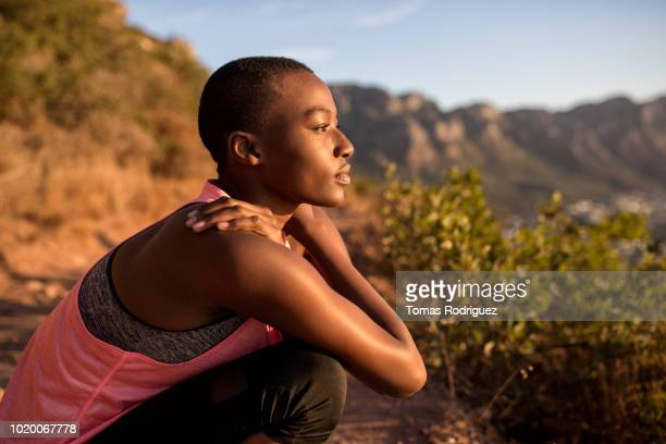 young woman taking a break on a hiking trip looking at view - femme africaine photos et images de collection