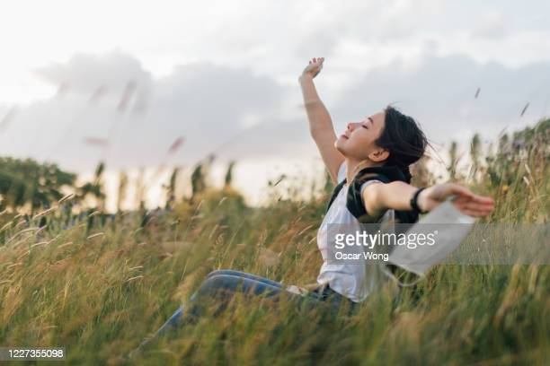 young woman taking a breath of fresh air after passing coronavirus - freedom stock pictures, royalty-free photos & images