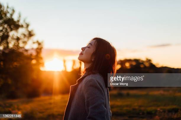 young woman taking a breath of fresh air in nature - hope stock pictures, royalty-free photos & images