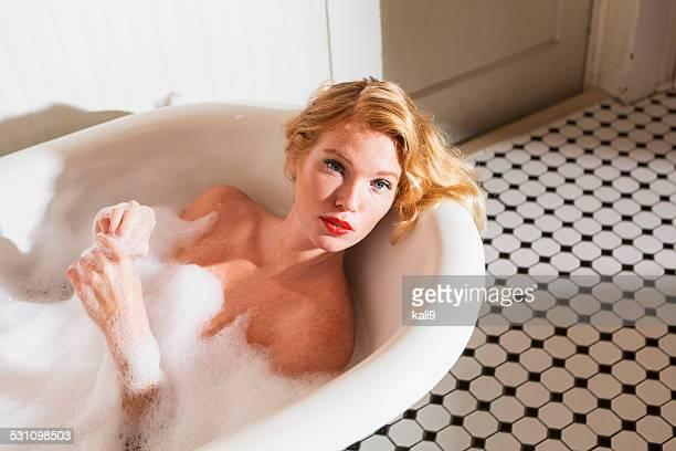 Young woman taking a bubble bath