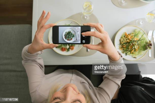 young woman taking a cell phone picture of a salad in a restaurant - influencer stock pictures, royalty-free photos & images