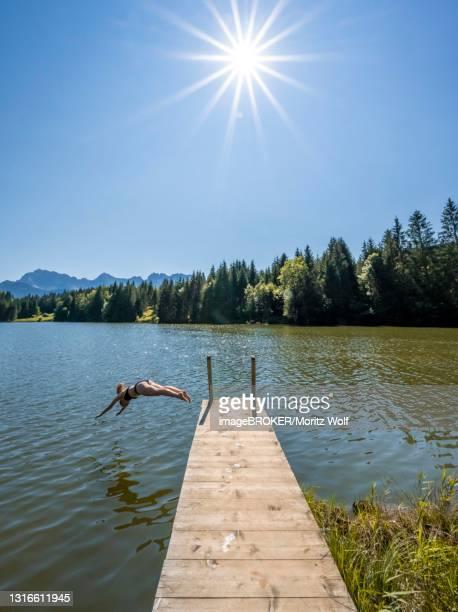 young woman taking a header into a lake, geroldsee, mittenwald, karwendel, bavaria, germany - mittenwald fotografías e imágenes de stock