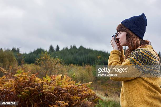 young woman taking a photo of the landscape - yellow hat stock pictures, royalty-free photos & images