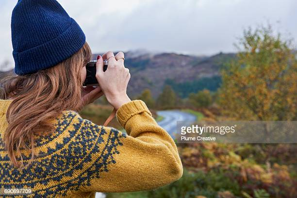 Young woman taking a photo of the landscape