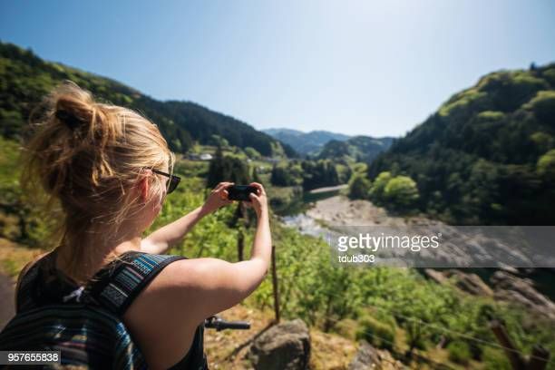Young woman taking a photo while cycling in the mountains