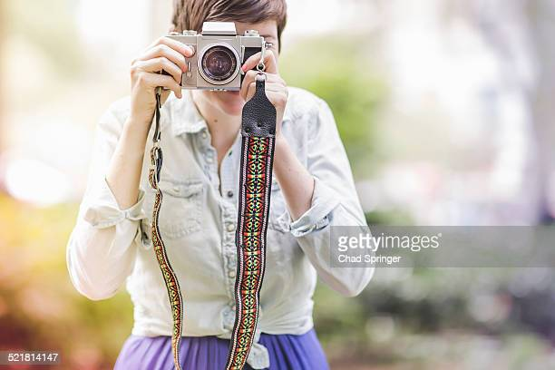 young woman taking a photograph - strap stock photos and pictures