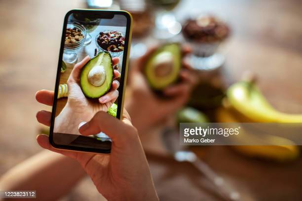 young woman taking a picture of fruit and vegetables - photographing stock pictures, royalty-free photos & images