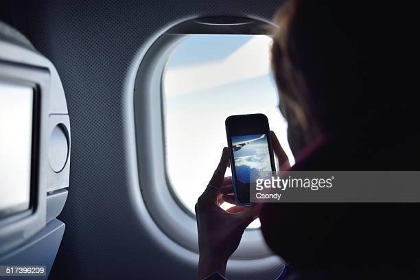 Joven mujer tomando una foto en un avión