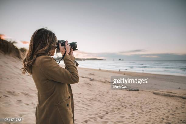 young woman taking a picture with a modern dslr camera - digital camera stock pictures, royalty-free photos & images