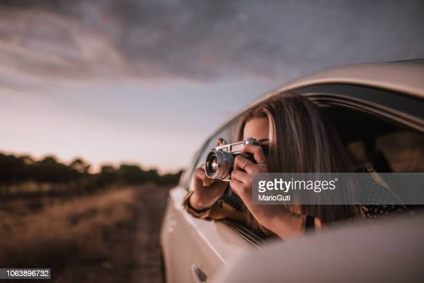 young woman taking a picture with a vintage camera from car window - photography themes stock pictures, royalty-free photos & images