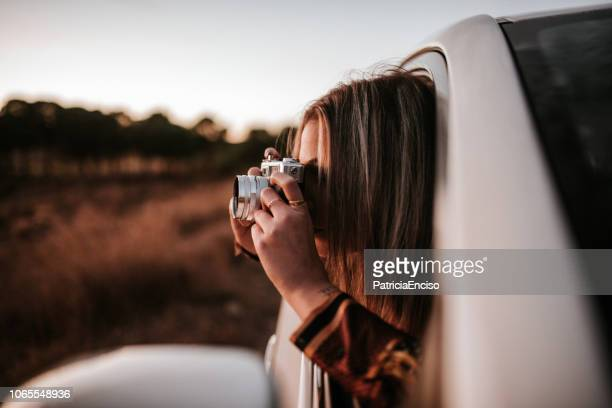 young woman taking a picture with a vintage camera from car window - estrada da vida imagens e fotografias de stock