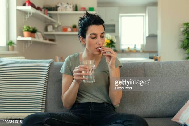 jonge vrouw die een pil neemt - medicijnen innemen stockfoto's en -beelden