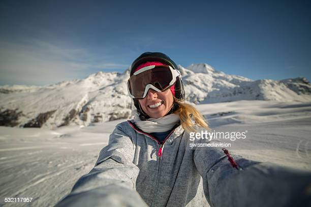 Young woman taking a selfie at top of mountain-Ski slopes