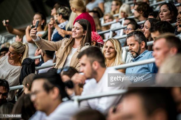 young woman taking a selfie during concert - sports event stock pictures, royalty-free photos & images