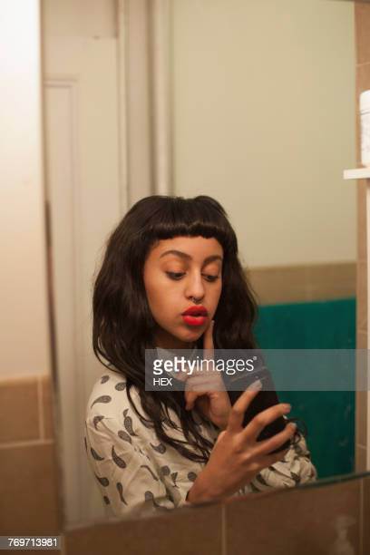 Young woman taking a selfie in her bathroom mirror