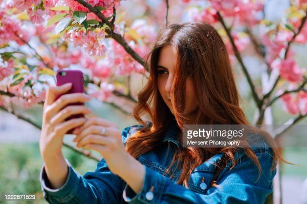 young woman taking a selfie in sakura background - audience free event stock pictures, royalty-free photos & images