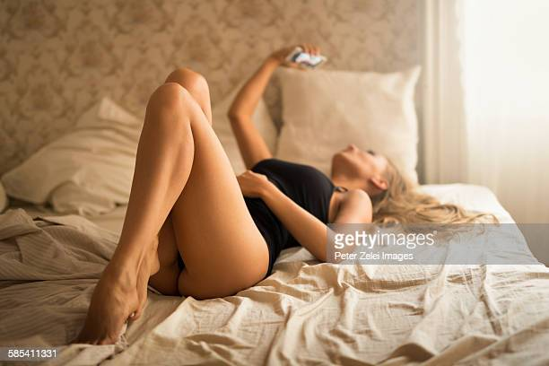 Young woman taking a selfie in the bed