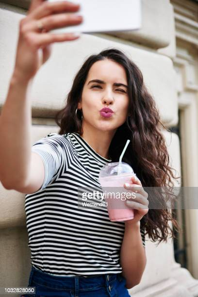 young woman taking a selfie in the city - puckering stock pictures, royalty-free photos & images