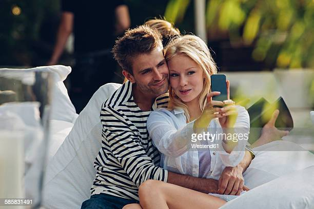 Young woman taking a selfie of herself and her boyfriend in an outdoor cafe