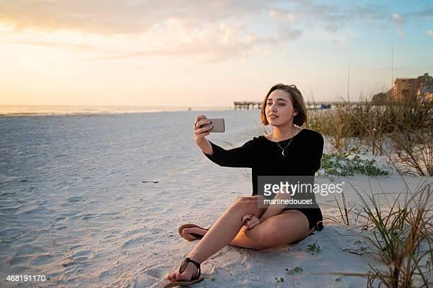 """joven mujer tomando un autorretrato en la playa al atardecer. - """"martine doucet"""" or martinedoucet fotografías e imágenes de stock"""