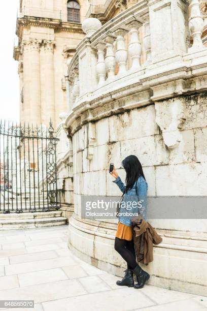 malaga, spain - december 18, 2016. young woman taking a selfie photo in front of the the renaissance cathedral in malaga, andalusia, spain - istock photo stock pictures, royalty-free photos & images