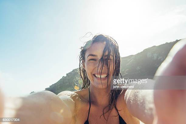 young woman taking a POV Selfie photograph on Porthcurno beach.