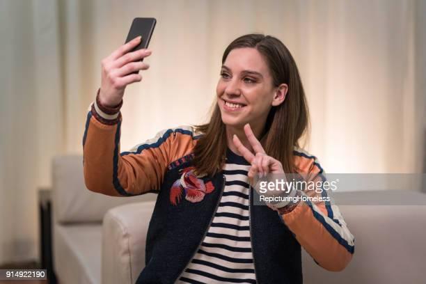 Eine Junge Frau posiert und lächelt für ein Selfie