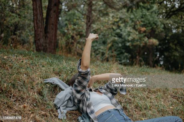a young woman taking a selfie while laying on ground - lying down stock pictures, royalty-free photos & images