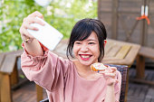 Young woman taking a selfie whilst holding a cupcake