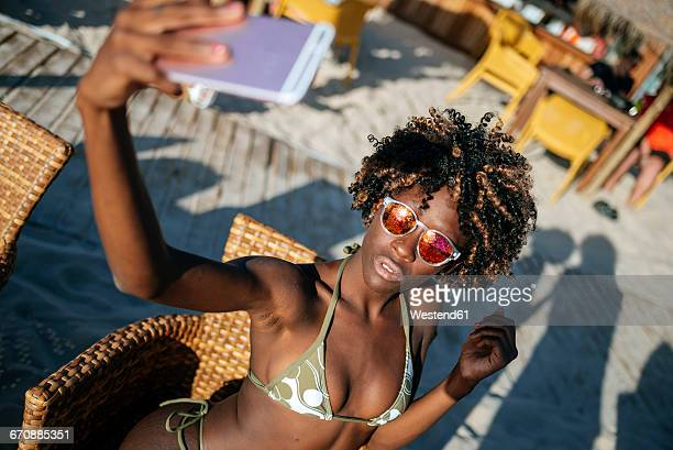 Young woman taking a selfie with a smartphone in a beach bar