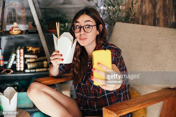 young woman taking a selfie with her chinese takeaways. - takeout stock pictures, royalty-free photos & images