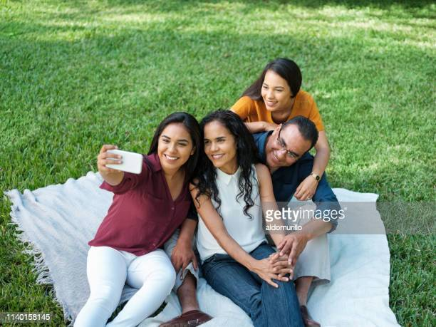 a young woman taking a selfie with her family - mexican picnic stock pictures, royalty-free photos & images