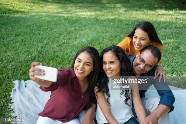 young woman taking a selfie with her family - mexican picnic stock pictures, royalty-free photos & images