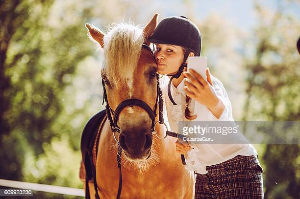 Young Woman taking a Selfie with her Horse